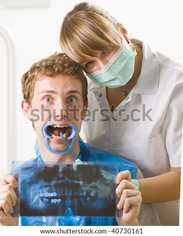 A dentist and her patient posing with funny facial expression.