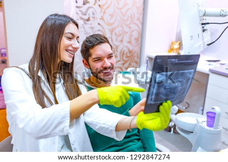 A dentist examines orthopantomogram in her hands. Dentist carefully examines the roentgenogram, white background. Rear view of female dentist looking at dental Xray in clinic