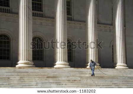 A Denver city worker spraying the steps of the Colorado Supreme Court Building. Can be used to illustrate cleaning up the justice system.