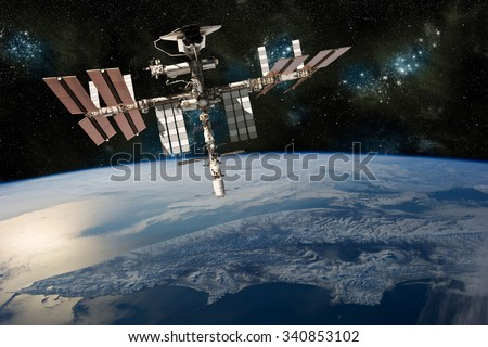A depiction of the space shuttle docked at the international space station orbiting Earth. -  Elements of this image furnished by NASA #340853102