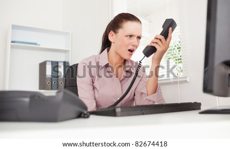 A depressed businesswoman shouting at telephone in her office