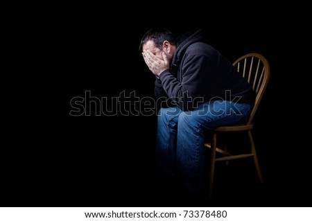 A depressed man sitting in a chair with his hands over his face, shot on black