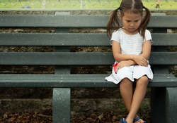 A depressed sad frustrated little girl sitting alone. Social anxiety and stressed children.