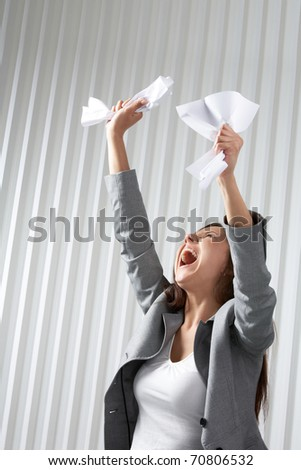 A depressed woman raising her hands with crumpled paper and screaming