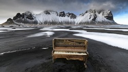 A derelict upright piano washed up on the black sand beach of the Stokksnes peninsula with the majestic, snow-capped Vestrahorn mountains in the background.