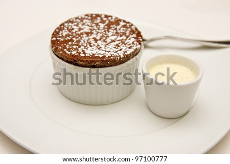A desert of a baked chocolate brownie in cup on a white plate with sweet sauce