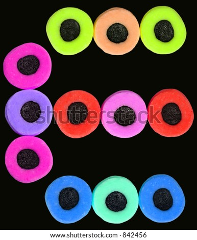 A design of twelve vividly colored liquorice allsorts sweets on a black background.