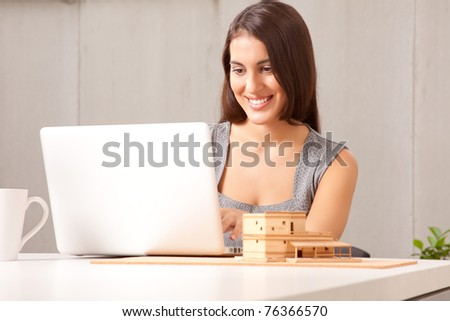 A designer or architect at desk with computer and model house