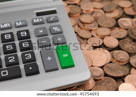 a desk Calculator with a green Equals button and Bank of england one pence and two pence Coins
