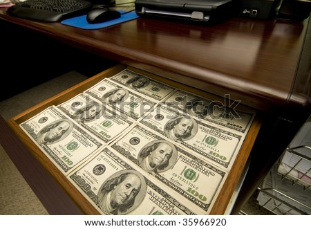 A Desk Drawer Stacked High with Hundred Dollar Bills.