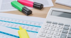A desk with financial documents and Highlighters