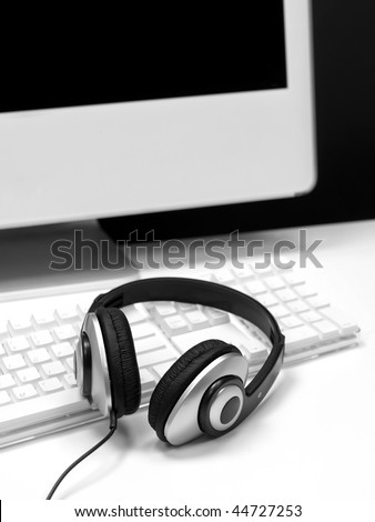 A desktop computer with a set of headphones isolated against a white background