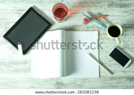 A desktop with a Tablet PC, a exercise book, a smartphone and various office supplies.