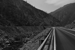 A desolate-looking California Highway 70 headed westward from Almanor, CA out of the Sierra Nevada mountains along the Feather River. The Union Pacific railway can be seen on the opposing bank.