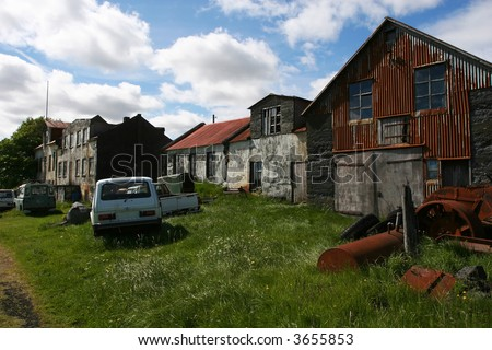 A desolate old farm in bad shape, rusting cars and machinery strewn across the lawn.