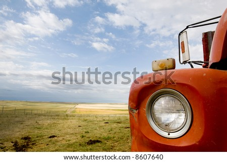 A detail and abstract of a grain truck and prairie landscape.