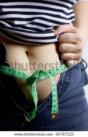 A detail of a belly of a fat woman who cannot wear her jeans and uses a measuring tailor type instead of a belt. - stock photo