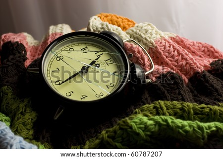 A detail of a broken alarm clock lying in colorful blankets.