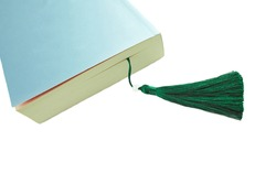 A detail of a closed book with a bookmark, isolated on pink background.