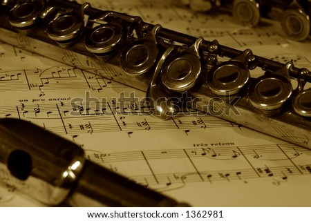 A detail of a flute resting on a sheet of music score