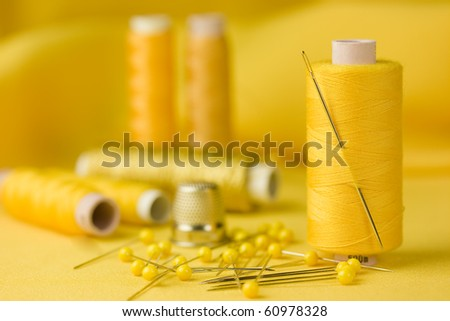 A detail of a sewing kit with cottons, pins and thimble on yellow background.