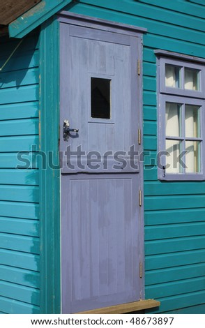 A detail of a turquoise wooden painted coastal beach hut. location in Christchurch, Hampshire UK.