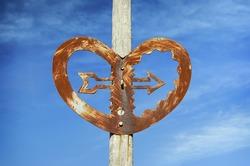 A detail of sculpture landmark in Wellington. A forged iron heart with an arrow  against a blue sky. Wellington, New Zealand.