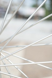 A detail of the spokes of a bicycle that make it look like a Ferris wheel.