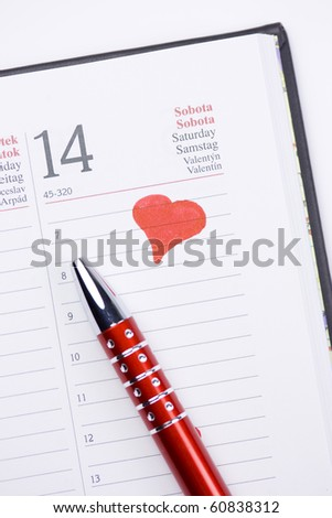 A detail of the Valentine day - February 14 page in a calendar with a red heart and a red decorated pen.