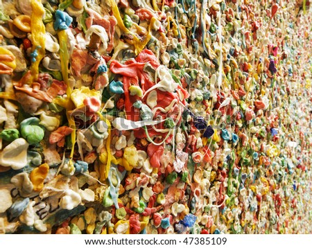 A detail view of part of the famous bubble gum wall in Post Alley near the Pike Place Market in Seattle. This landmark has built up layers of chewing gum over the years in colorful abstract pattern.
