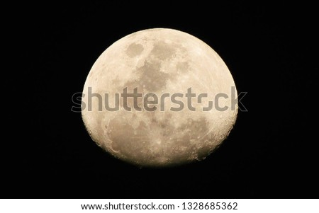 A detailed close up picture of the moon in a black background. Full moon.