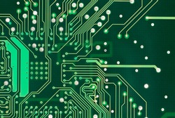 A detailed image of a small green microchip circuit board.
