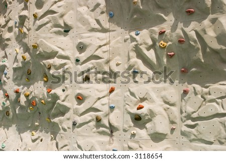 A detailed view of an artificial climbing wall with multi-colored holds spread throughout the wall. A close look shows two cables used for belaying.