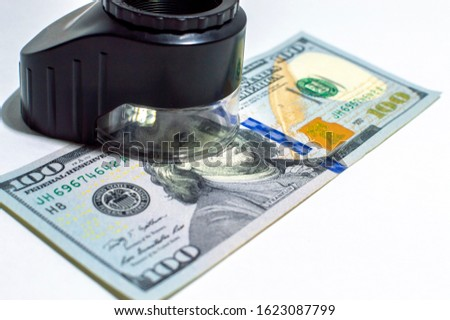 a device (magnifier) for banknote authentication and a hundred-dollar bill on a white background.