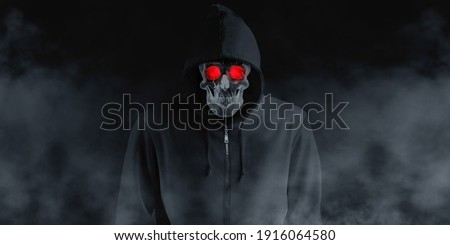 A devil skull in a black robe with a hood and a smoke skull smiling under a black shirt. The spirit in the coat Black background with smog 3d illustration Photo stock ©