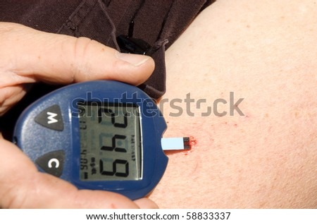 A diabetic checking blood sugar levels with a metering device