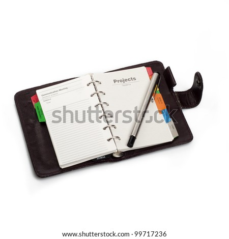 "A diary opened at page of ""Projects"" with pen that hold on it. Isolated on white background"