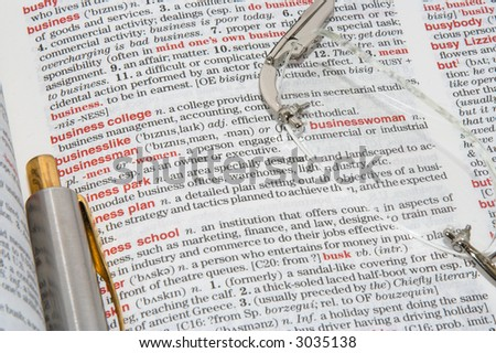 A dictionary opened at different business definitions with a pen and glasses on it - stock photo