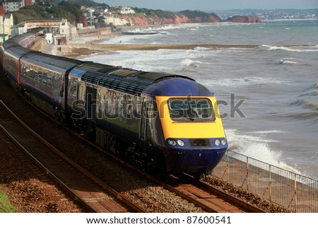 A diesel engine passes through dawlish station on the famous Brunel South Devon coastal route