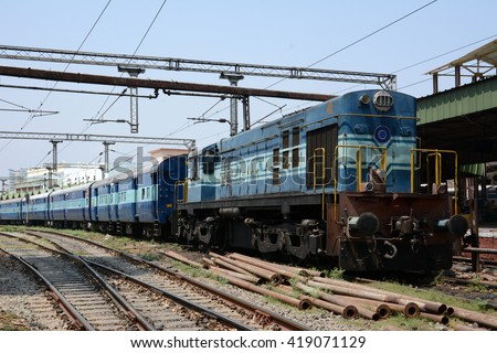 A diesel locomotive hauling a passenger train through a railway station in India.