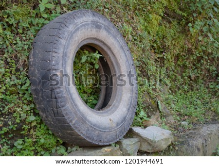 A dilapated flat rubber tier left over the side of the road in Ukhimath, Uttarakhand