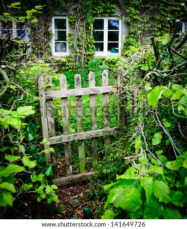 A dilapidated cottage gate with quaint cottage in the background in England, UK at summertime