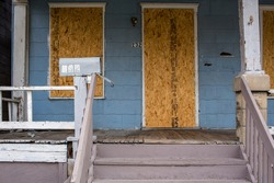 A dilapidated foreclosed home sits boarded up and empty