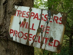 A dilapidated rusty old vintage , Trespassers Will Be Prosecuted sign of Red letters on a white background in the English countryside.