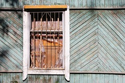 A dilapidated wooden abandoned house. Old building. Uninhabited house. A boarded-up window and no one there. A broken window close-up. The grating on the broken window. Realty.