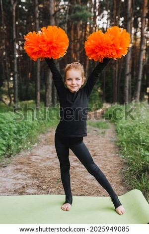 A diligent, smiling girl, a child cheerleader in a black suit is dancing in the woods in nature with big orange pom-poms in her hands. Sports training for cheerleading. ストックフォト ©