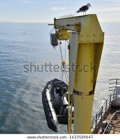 A dinghy boat being hoisted onto a dock by a crane