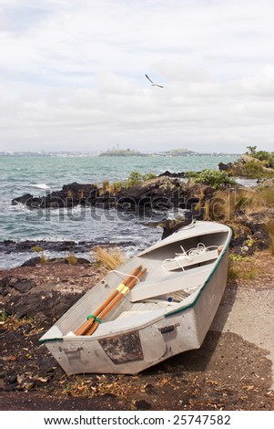 A dinghy rests on the shore of Rangitoto Island in the Hauraki Gulf of New Zealand. Auckland City is in the distance.