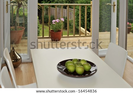 a dining room with entrance to patio and garden - stock photo