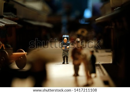 A diorama depicting a Japanese merchant walking through a crowd in a busy street